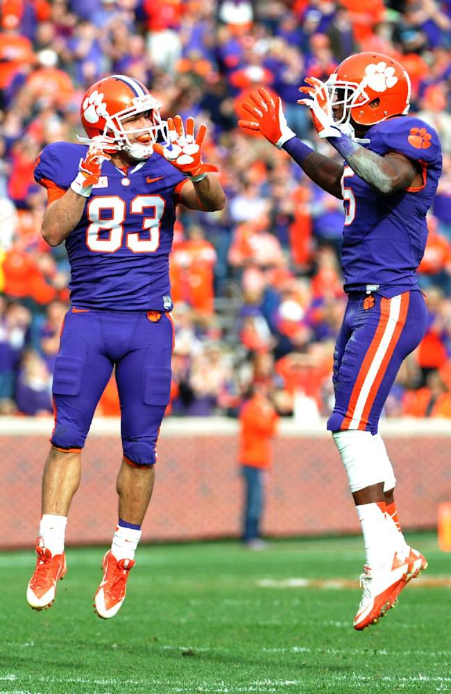 Clemson wide receiver Daniel Rodriguez (83) celebrates his touchdown with wide receiver Germone Hopper (5) during the second half of an NCAA college football game against The Citadel, Saturday, Nov. 23, 2013, in Clemson, S.C. Rodriguez, an Army veteran and Purple Heart recipient, is a walk-on player for Clemson