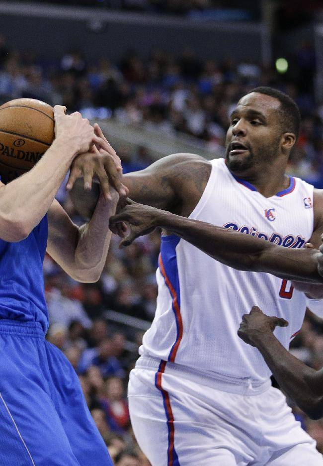 Dallas Mavericks' Dirk Nowitzki, left, gets a rebound against Los Angeles Clippers' Darren Collison, right, and Glen Davis during the first half of an NBA basketball game on Thursday, April 3, 2014, in Los Angeles