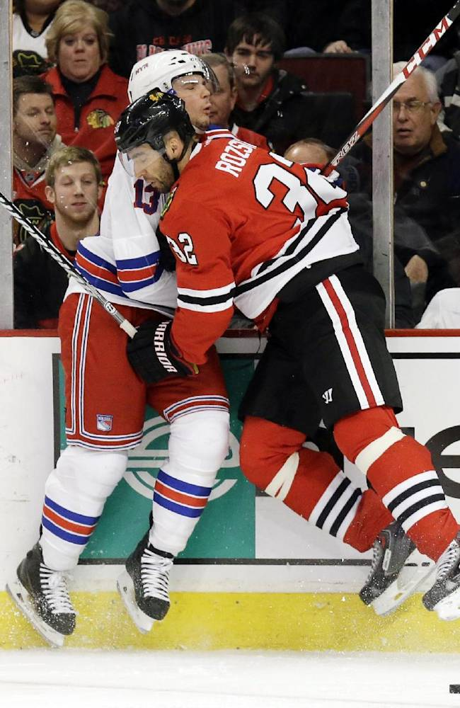 New York Rangers' Daniel Carcillo, left, is checked by Chicago Blackhawks' Michal Rozsival during the first period of an NHL hockey game in Chicago, Wednesday, Jan. 8, 2014