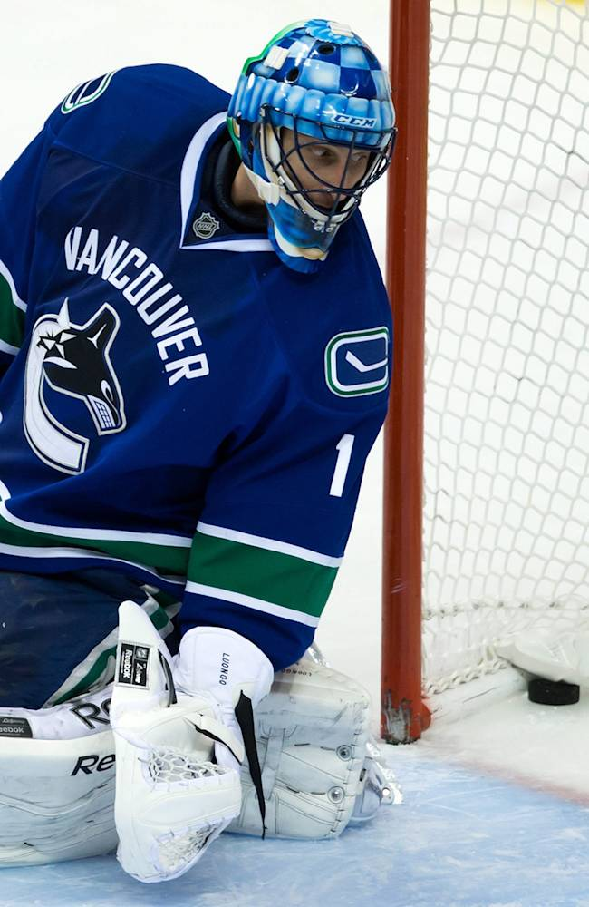 Vancouver Canucks' goalie Roberto Luongo looks back at the puck after allowing a goal to Chicago Blackhawks' Andrew Shaw during third period NHL hockey action in Vancouver British Columbia Saturday Nov. 23, 2013