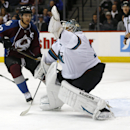 San Jose Sharks goalie Antti Niemi, front, of Finland, reaches up to make glove save as Colorado Avalanche left wing Gabriel Landeskog, of Sweden, covers in the first period of an NHL hockey game in Denver on Tuesday, Oct. 28, 2014 The Associated Press