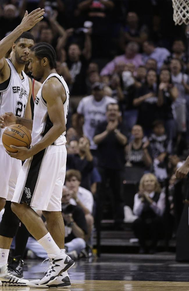 San Antonio Spurs' Tim Duncan (21) celebrates with teammate Kawhi Leonard, center, as Portland Trail Blazers' LaMarcus Aldridge, right, looks on during the second half of Game 2 of a Western Conference semifinal NBA basketball playoff series, Thursday, May 8, 2014, in San Antonio. San Antonio won 114-97