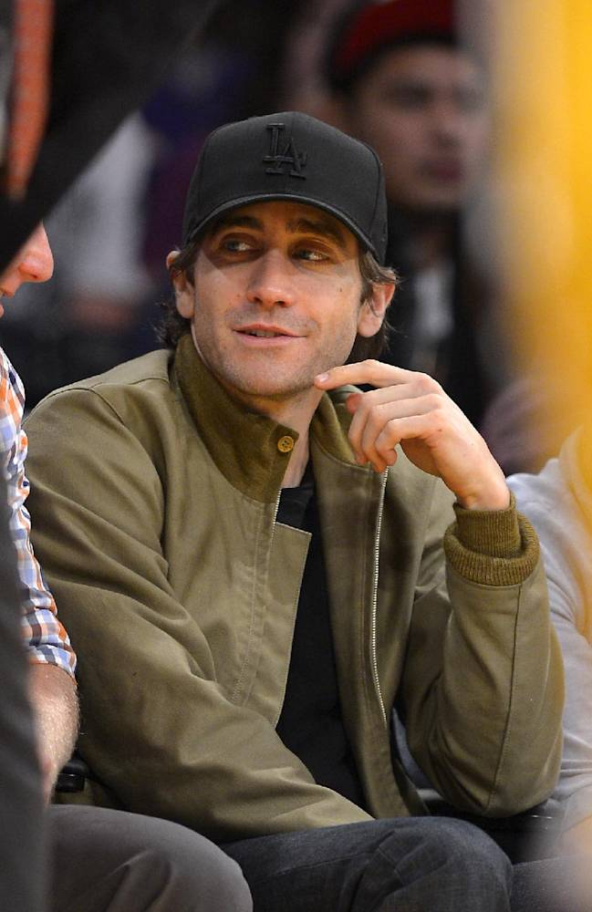 Actor Jake Gyllenhaal watches the Los Angeles Lakers play the Minnesota Timberwolves during the first half of an NBA basketball game, Sunday, Nov. 10, 2013, in Los Angeles