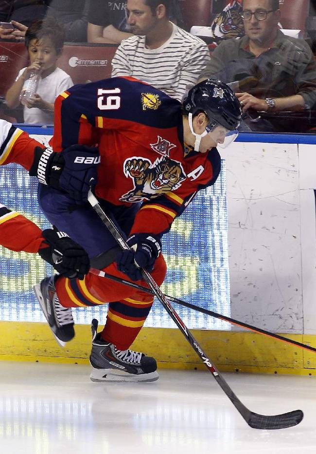 Calgary Flames defenseman Mark Giordano (5) and Florida Panthers right wing Scottie Upshall (19) fight for the puck during the first period of an NHL hockey game in Sunrise, Fla., on Friday, April 4, 2014