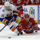New York Islanders' Kyle Okposo (21) and Carolina Hurricanes' Brad Malone (24) chase the puck during the second period of an NHL hockey game in Raleigh, N.C., Friday, Oct. 10, 2014 The Associated Press
