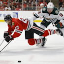 Chicago Blackhawks defenseman Johnny Oduya (27) battles for the puck with Minnesota Wild center Ryan Carter (18) during the first period of an NHL hockey game in Chicago, Sunday, Jan. 11, 2015 The Associated Press