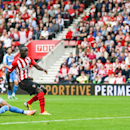 Southampton's Sadio Mane, center, scores his side's eighth goal despite the attentions of Sunderland's Patrick van Aanholt during the English Premier League soccer match at St. Mary's Stadium, Southampton, England, Saturday, Oct. 18, 2014