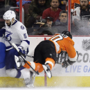 Philadelphia Flyers' Brayden Schenn, right, flies into the boards after colliding with Tampa Bay Lightning's Jason Garrison during the third period of an NHL hockey game, Monday, Jan. 12, 2015, in Philadelphia. Philadelphia won 7-3 The Associated Press