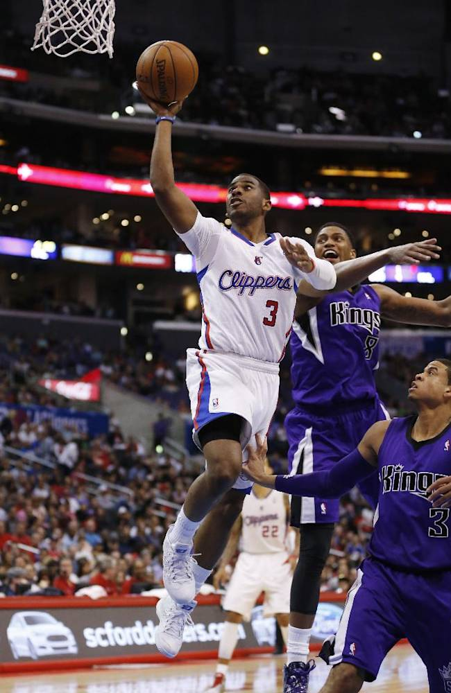 CORRECTS DAY OF WEEK TO SATURDAY - Los Angeles Clippers guard Chris Paul shoots the ball in front of Sacramento Kings forward Rudy Gay, second right, and Kings guard Ray McCallum, right, during the first half of an NBA basketball game in Los Angeles, Saturday, April 12, 2014