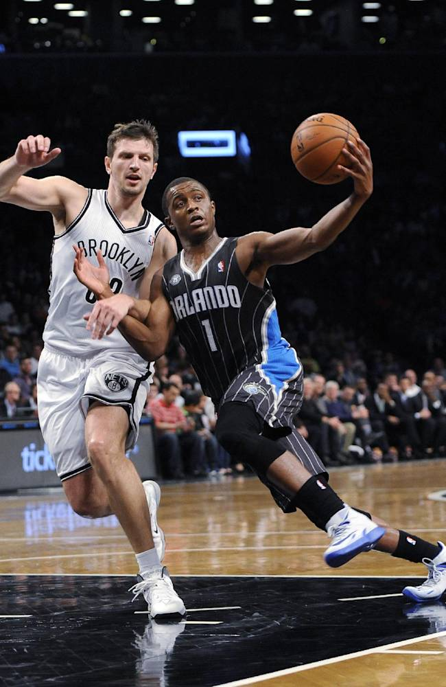 Brooklyn Nets' Mirza Teletovic (33) defends Orlando Magic's Doron Lamb (1) duirng the second half of an NBA basketball game Sunday, April 13, 2014, in New York. The Nets won 97-88