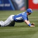 Kansas City Royals' Johnny Giavotella dives but is unable to come up with a ball hit by Los Angeles Angels' Mike Trout during the first inning of a spring training baseball game Friday, March 21, 2014, in Tempe, Ariz The Associated Press