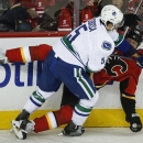 Vancouver Canucks' Luca Sbisa, left, from Italy, takes out Calgary Flames' Brian Mcgrattan during first period NHL hockey action in Calgary, Alberta, Wednesday, Oct. 8, 2014 The Associated Press