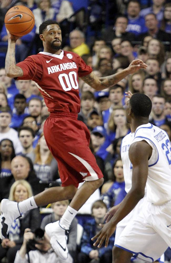 Arkansas' Rashad Madden looks for an open teammate as Kentucky's Alex Poythress (22) watches during the first half of an NCAA college basketball game Thursday, Feb. 27, 2014, in Lexington, Ky