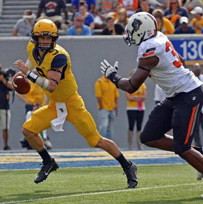 West Virginia quarterback Clint Trickett (9) avoids the pass rush in the third quarter of an NCAA college football game against Oklahoma State in Morgantown, W.Va., on Saturday, Sept. 28, 2013