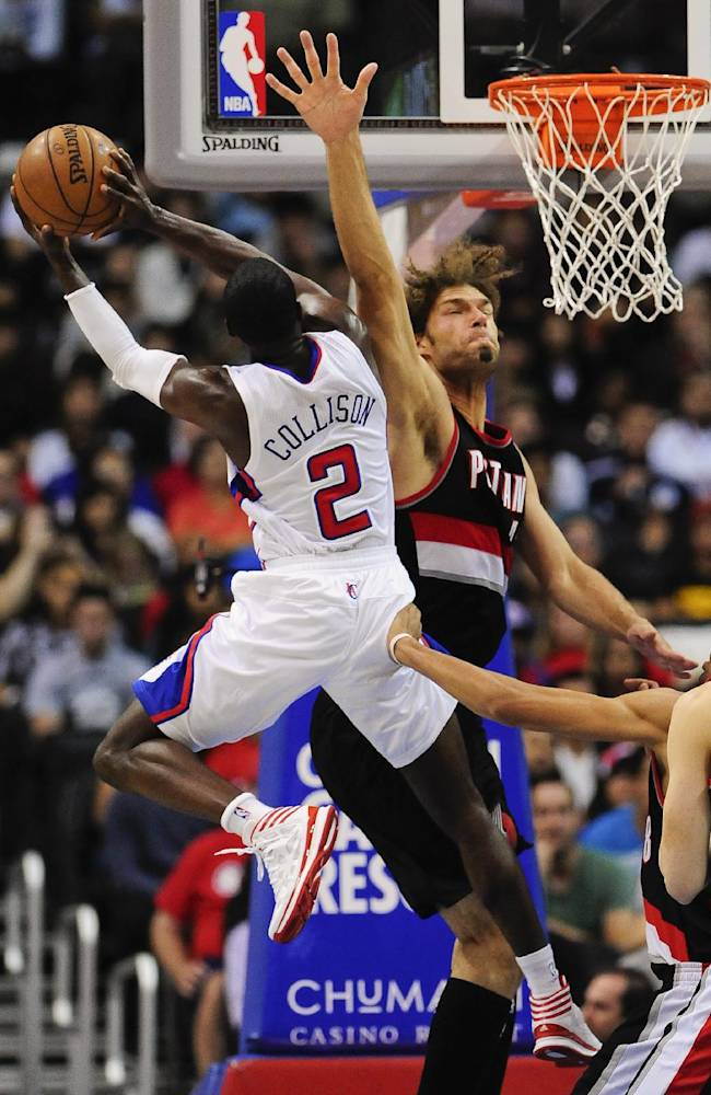 Los Angeles Clippers guard Darren Collison (2) drives on Portland Trail Blazers center Robin Lopez, right, as he drives to the basket in the first half of a pre-season NBA basketball game, Friday, Oct. 18, 2013, in Los Angeles