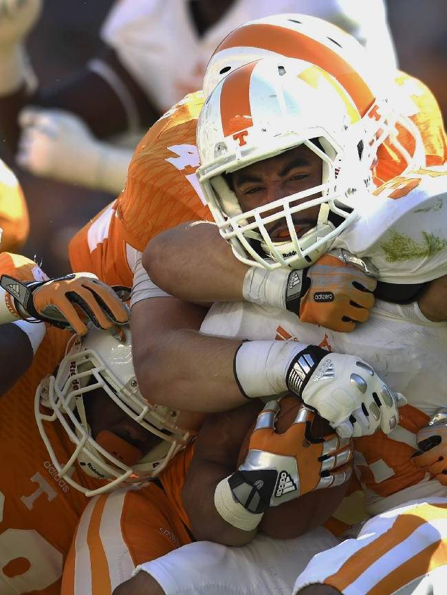 Tennessee running back Justus Pickett (31) is tackled by Tennessee defense while carrying the ball during the second half of the Orange and White game at Neyland Stadium in Knoxville, Tenn., Saturday, April 12, 2014