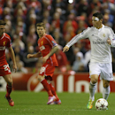 Real Madrid's James Rodriguez, right, runs with the ball during the Champions League group B soccer match between Liverpool and Real Madrid at Anfield Stadium, Liverpool, England, Wednesday Oct. 22, 2014