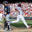 Philadelphia Phillies' Carlos Ruiz, right, scores on the single by Marlon Byrd with Milwaukee Brewers catcher Jonathan Lucroy looking onto the field during the first inning of an MBL baseball game on Tuesday, April 8, 2014, in Philadelphia The Associated