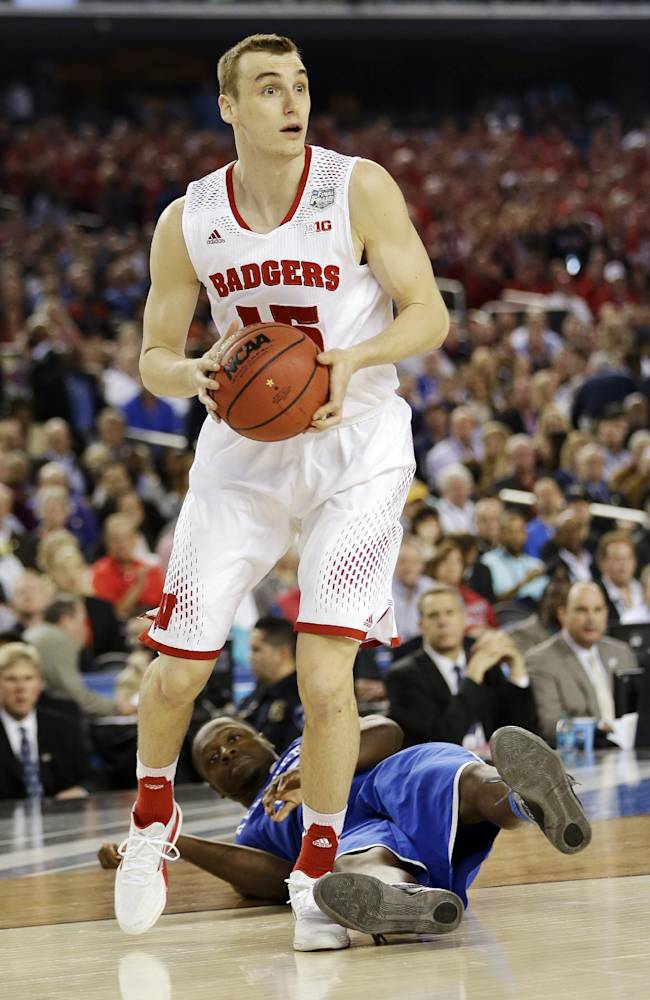 Wisconsin forward Sam Dekker (15) controls the ball as Kentucky forward Julius Randle hits the floor during the second half of the NCAA Final Four tournament college basketball semifinal game Saturday, April 5, 2014, in Arlington, Texas
