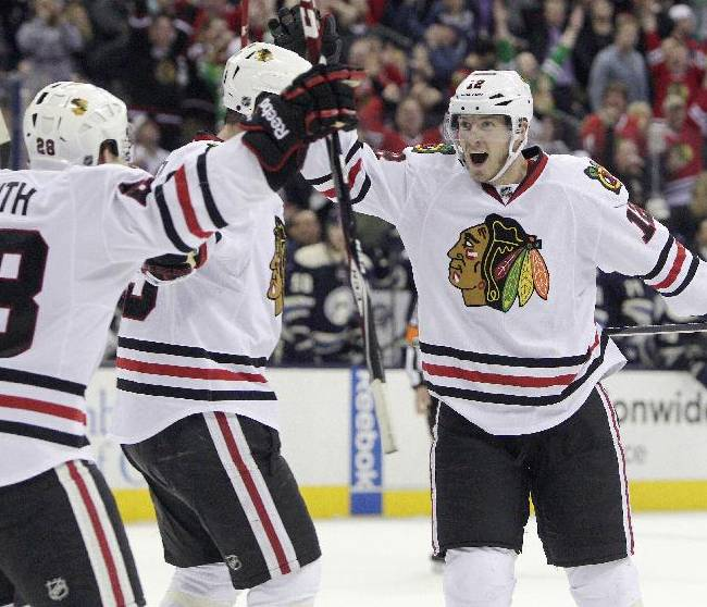 Chicago Blackhawks' Peter Regin, right, of Denmark, celebrates their goal against the Columbus Blue Jackets with teammates Ben Smith, left, and Bryan Bickell during the third period of an NHL hockey game on Friday, April 4, 2014, in Columbus, Ohio. The Blackhawks defeated the Blue Jackets 4-3