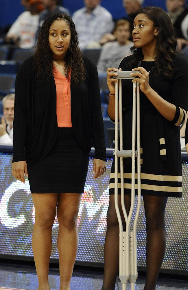 Connecticut's Kaleena Mosqueda-Lewis, left, and Morgan Tuck watch their team warm up for an NCAA college basketball game against Central Florida, Wednesday, Feb. 19, 2014, in Hartford, Conn. Mosqueda-Lewis is out with mononucleosis and Tuck is out for the season with a knee injury