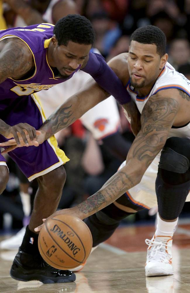 Los Angeles Lakers' Manny Harris, left, and New York Knicks' Jeremy Tyler fight for the ball during the second half of an NBA basketball game at Madison Square Garden Sunday, Jan. 26, 2014, in New York. The Knicks won 110-103