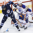 Winnipeg Jets' Dustin Byfuglien (33) deflects the puck to score the game-tying goal against the Edmonton Oilers during the third period of an NHL hockey game in Winnipeg on Wednesday, Dec. 3, 2014 The Associated Press
