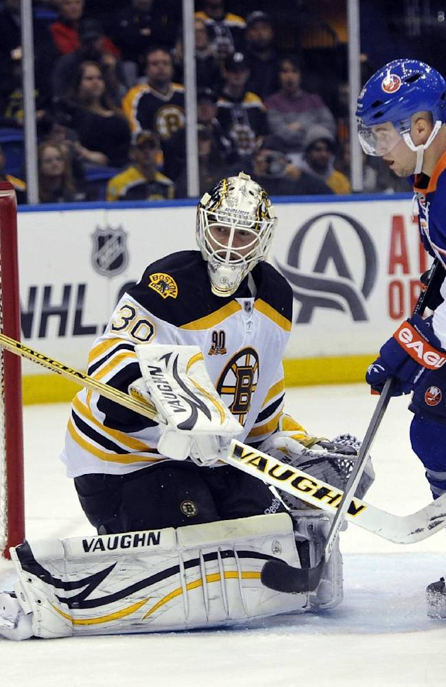 Boston Bruins goalie Chad Johnson (30) and New York Islanders' Pierre-Marc Bouchard (96) watch the puck bounce off Johnson's knee pad in the second period of an NHL hockey game at the Nassau Coliseum on Saturday, Nov. 2, 2013, in Uniondale, N.Y