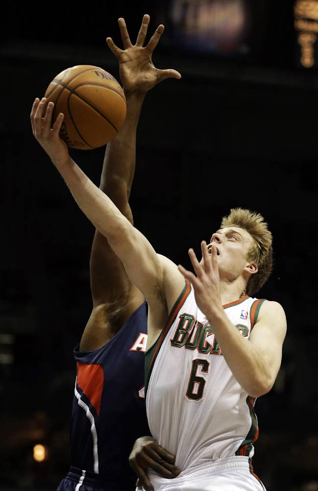 Milwaukee Bucks' Nate Wolters, right, puts up a shot against the Atlanta Hawks during the second half of an NBA basketball game Saturday, Jan. 25, 2014, in Milwaukee
