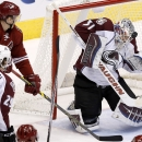 Colorado Avalanche's Calvin Pickard (31) plays a shot by Arizona Coyotes' Lauri Korpikoski (28), of Finland, off his face mask as Avalanche's Nathan MacKinnon (29) looks on during the second period of an NHL hockey game Tuesday, Nov. 25, 2014, in Glendale