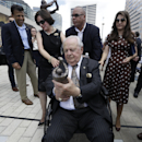 New Orleans Saints owner Tom Benson holds a miniature replica of a statue of him during an unveiling ceremony outside the Mecedes-Benz Superdome in New Orleans, Tuesday, Sept. 2, 2014. Behind him are Louisiana Gov. Bobby Jindal, left, Benson's wife Gayle