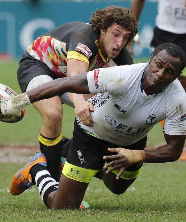 Fiji's Pio Tuwai, right, is tackled by England's Dan Bibby during their semifinal match of the Hong Kong Sevens rugby tournament in Hong Kong, Sunday, March 30, 2014. England won 17-7