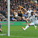 Hull City's Shane Long, second left, has a shot on goal during the English Premier League soccer match between Hull City and Swansea City at the KC Stadium, Hull, England, Saturday, April 5, 2014