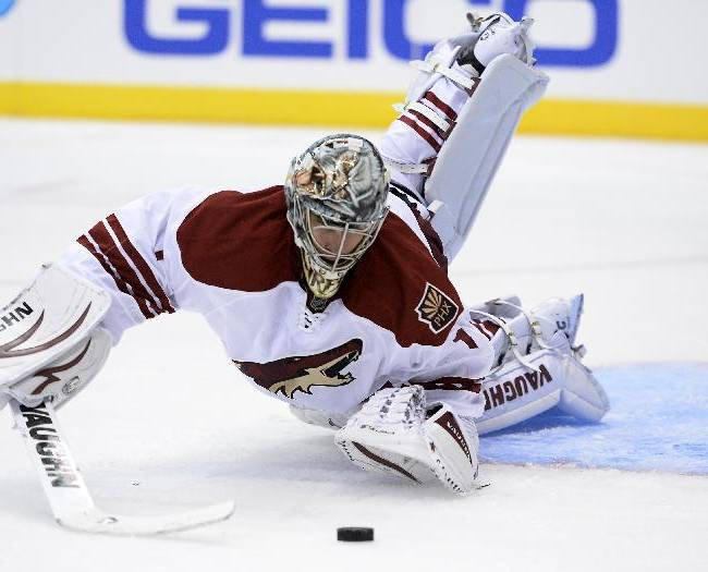 Phoenix Coyotes goalkeeper Thomas Greiss (1) dives to make a save against Los Angeles Kings during the second period of an NHL hockey game at the Staples Center Sunday, April 15, 2013., in Los Angeles