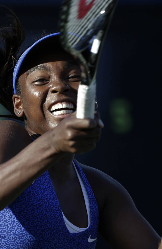 Francoise Abanda, of Canada, returns a shot against Sabine Lisicki, of Germany, during the opening round of the 2014 U.S. Open tennis tournament, Monday, Aug. 25, 2014, in New York