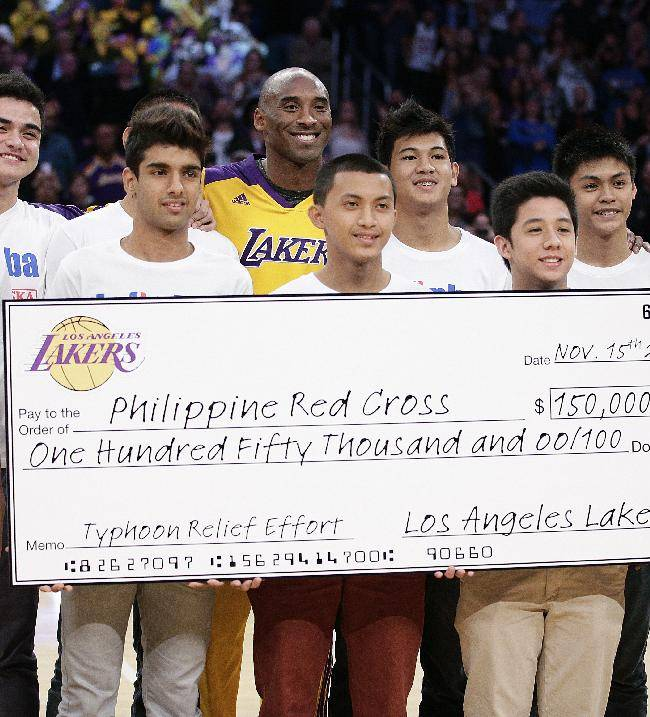 Los Angeles Lakers' Kobe Bryant, center, poses with young basketball players from the Philippines as he presents the Los Angeles Lakers' donation check to the the Philippine Red Cross during an NBA basketball game between the Los Angeles Lakers and the Memphis Grizzlies on Friday, Nov. 15, 2013, in Los Angeles