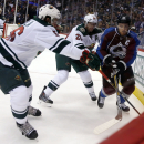 Minnesota Wild center Erik Haula, left, of Finland and defenseman Ryan Suter, center, pursue Colorado Avalanche left wing Gabriel Landeskog, of Sweden, as he tries to move the puck in the corner in the second period of an NHL hockey game in Denver on Satu