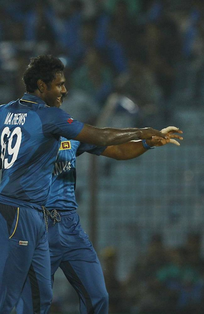 Sri Lanka's Ajantha Mendis, left, celebrates with his teammate captain Dinesh Chandimal, rear, after the wicket of Netherlands's Peter Borren, right, during their ICC Twenty20 Cricket World Cup match in Chittagong, Bangladesh, Monday March 24, 2014