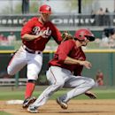 Cincinnati Reds shortstop Zack Cozart tags out Arizona Diamondbacks' Nick Ahmed on a rundown between first and second in the fifth inning of a spring exhibition baseball game Thursday, March 27, 2014, in Goodyear, Ariz The Associated Press