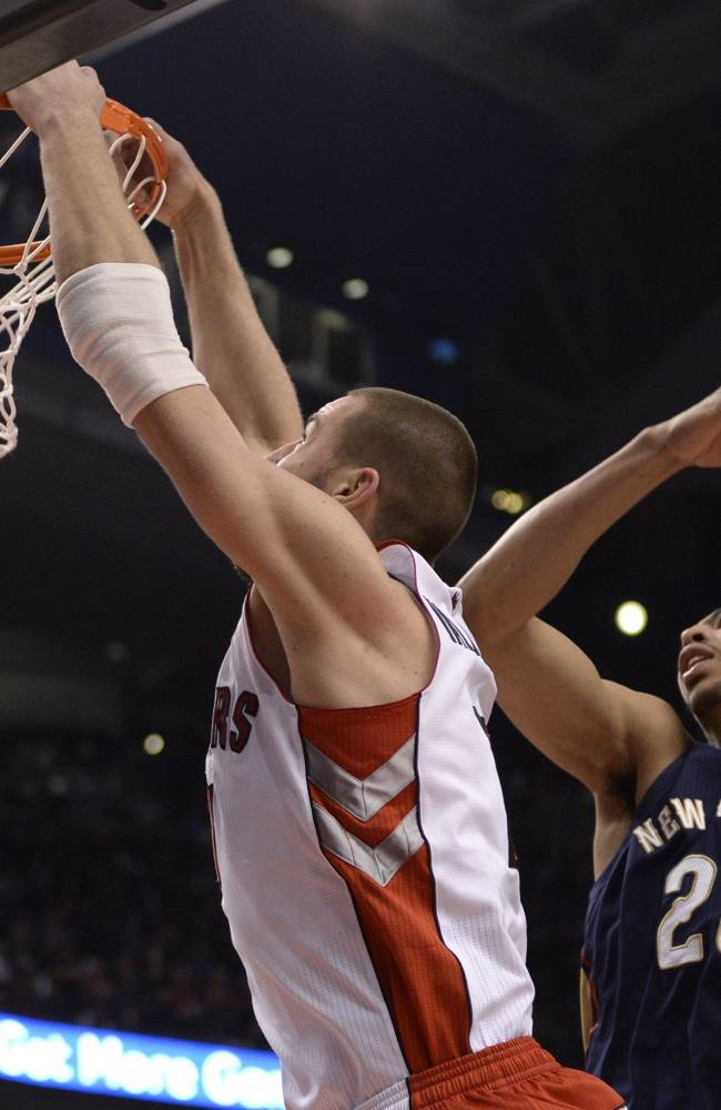 Toronto Raptors' Jonas Valanciunas dunks the ball as New Orleans Pelicans' Anthony Davis trails him, during first quarter NBA action in Toronto, Monday, Feb. 10, 2014