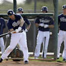 San Diego Padres' Carlos Quentin swings at a pitch in batting practice as other players wait their turn outside the cage during spring training baseball practice, Friday, Feb. 21, 2014, in Peoria, Ariz The Associated Press