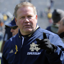 Notre Dame coach Brian Kelly heads off the field after the Blue-Gold spring NCAA college football game, Saturday, April 20, 2013, in South Bend, Ind. Kelly was wearing a yellow ribbon to honor those injured and killed in the Boston Marathon bombings.(AP Photo/Joe Raymond)