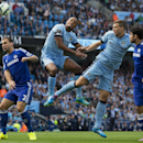 Manchester City's Edin Dzeko, second right and Vincent Kompany, centre left, jump for a ball as Chelsea's Branislav Ivanovic, left, and Diego Costa look on during their English Premier League soccer match at the Etihad Stadium, Manchester, England, Sunday
