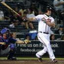 Atlanta Braves' Chipper Jones follows through on a double in front of Chicago Cubs catcher Steve Clevenger during the sixth inning of a baseball game Tuesday, July 3, 2012, at Turner Field in Atlanta. (AP Photo/David Tulis)