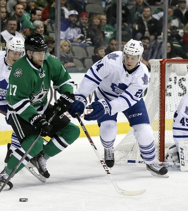 Dallas Stars center Rich Peverley (17) controls the puck , ooking for a shot opportunity, as Toronto Maple Leafs' Morgan Rielly (44) and Peter Holland (24) help goalie Jonathan Bernier (45) during the first period of an NHL hockey game, Thursday, Jan. 23, 2014, in Dallas