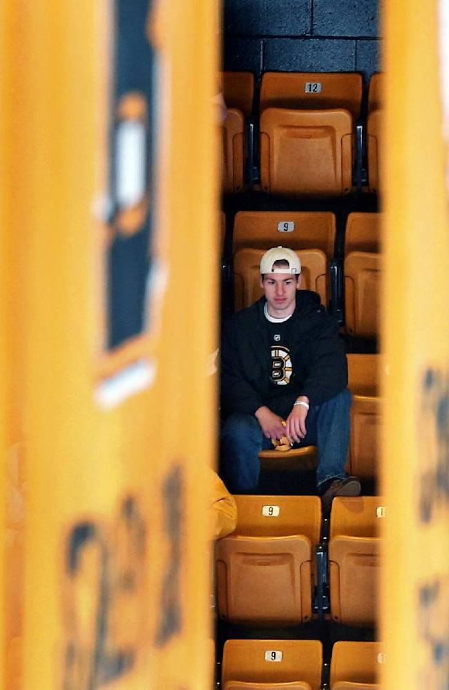 A Boston Bruin fan waits for the start of Game 5 in the first round of the NHL hockey Stanley Cup playoffs between the Bruins and the Detroit Red Wings in Boston, Saturday, April 26, 2014