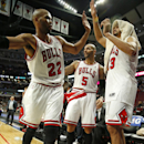 Chicago Bulls forward Taj Gibson (22) celebrates the win against the Miami Heat with forward Carlos Boozer (5) and center Joakim Noah (13) at the end of an NBA basketball game in Chicago, Thursday, Dec. 5, 2013. The Bulls defeated the Heat 107-87 The Asso