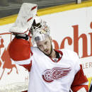 Detroit Red Wings goalie Jonas Gustavsson, of Sweden, pulls on his mask during a break the second period of an NHL hockey game against the Nashville Predators Saturday, Feb. 28, 2015, in Nashville, Tenn. (AP Photo/Mark Humphrey)