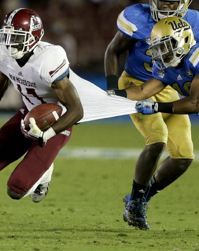 UCLA defensive back Charles Dawson, right, pulls New Mexico State wide receiver Jerrel Brown down by the jersey during the second half of an NCAA college football game Saturday, Sept. 21, 2013, in Pasadena, Calif. UCLA won 59-13