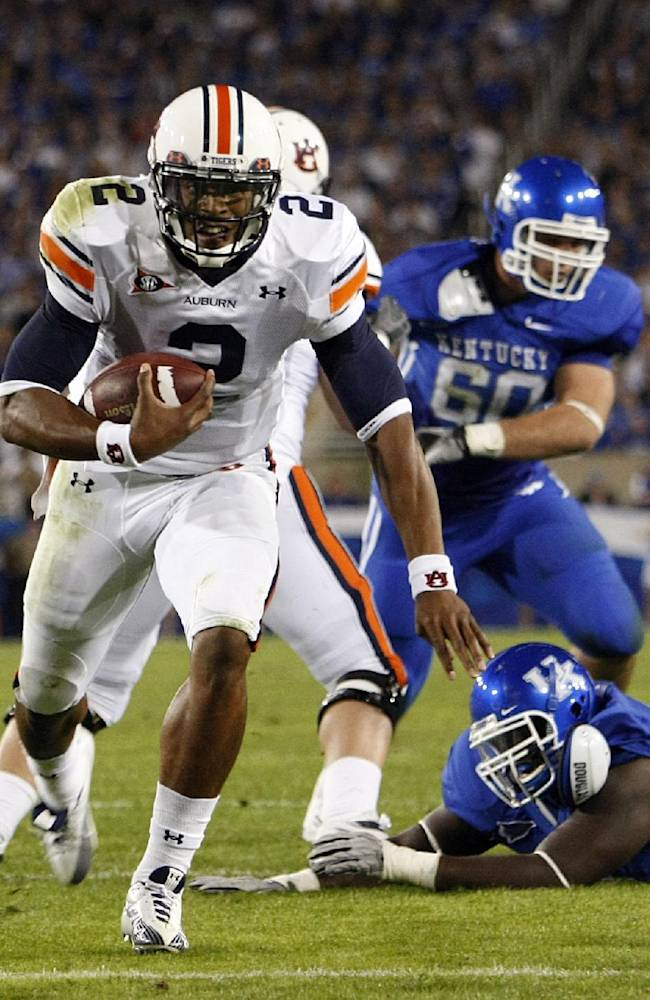 In this Oct. 9, 2010, file photo, Auburn quarterback Cameron Newton eyes the end zone on his second touchdown run during the first half of an NCAA college football game against Kentucky in Lexington, Ky. Auburn coach Gus Malzahn knows the luxury of having the rare quarterback who can take over games and baffle defenses with his arm or his feet. For Malzahn, it was Newton. On Saturday, his Tigers are charged with trying to slow down No. 7 Texas A&M's Johnny Manziel